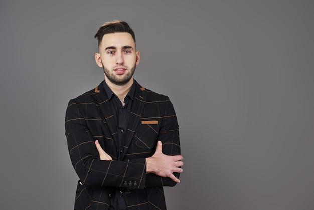 Exitoso joven empresario en un traje marrón con una encantadora sonrisa genuina posando contra un gris oscuro