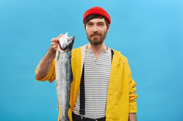 Exitoso pescador barbudo de pie sobre una pared azul con su captura con expresión feliz. apuesto joven sosteniendo un pez largo y pesado en las manos sintiéndose orgulloso y emocionado
