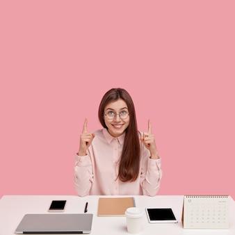 Exitoso y próspero joven empresario con mirada alegre, apunta con ambos dedos índices al techo, viste camisa elegante y gafas