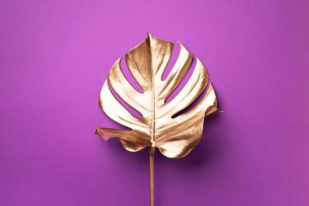 Exótica tendencia veraniega en estilo minimalista. hoja de monstera de palma tropical dorada