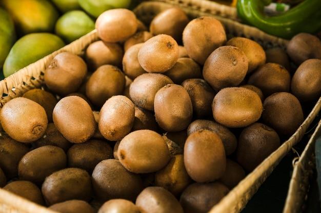 Exótico kiwi orgánico en canasta de mimbre en el mercado