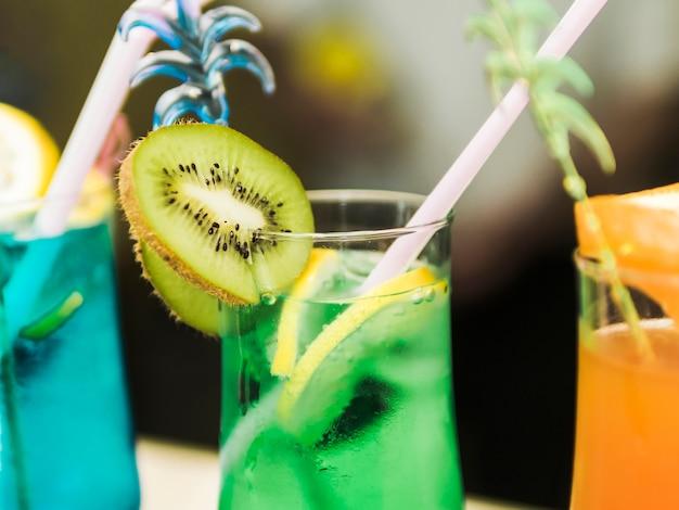 Exóticos cócteles fríos de colores con frutas y pajitas.