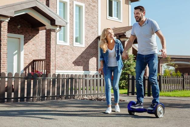 Experiencia emocionante. encantador joven montando un scooter de equilibrio automático por primera vez y sosteniendo la mano de su esposa, buscando apoyo