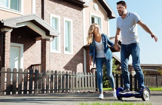 Experiencia inolvidable. hombre joven lleno de alegría montando un hoverboard y gritando de emoción mientras sostiene la mano de su esposa, buscando apoyo