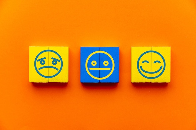 Experiencia de servicio al cliente y concepto de encuesta de satisfacción con expresiones faciales negativas, neutrales y positivas en el cubo de madera en la mesa, fondo naranja