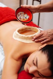 Experimentar el tratamiento ayurveda. mujer de cabello oscuro que se somete a un procedimiento de kati vasti en el salón de spa mientras domina la construcción con aceite aromático
