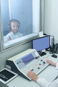 Experimente, escuche. niña sonriente en auriculares detrás de un vidrio en la oficina especial y manos del otorrinolaringólogo cerca del equipo