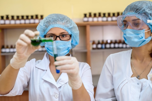 Experimento químico dos mujeres en uniforme protector con tubos de ensayo en laboratorio