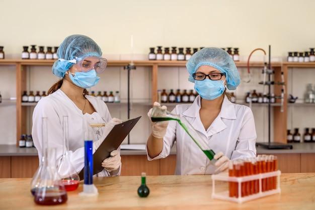 Experimento químico en laboratorio. dos químicos examinando el matraz con sustancia líquida