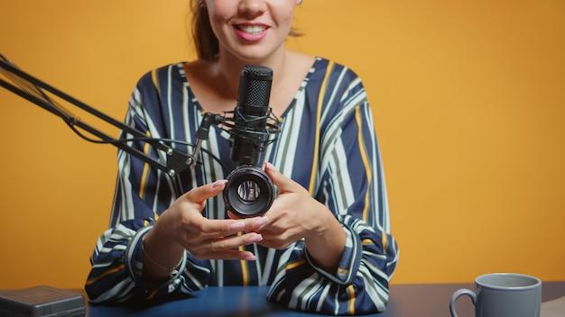 Experta en fotografía hablando sobre lentes de cámara en su podcast semanal para suscriptores. creador de contenido, influenciador estrella de los nuevos medios en las redes sociales, hablando, equipo de fotos de video para un programa web en línea