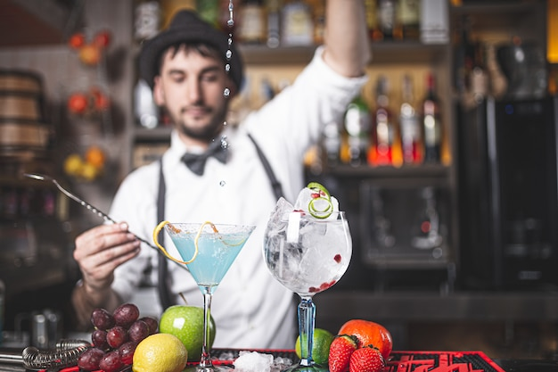Experto barman haciendo un cóctel en el club nocturno con sombrero y pajarita