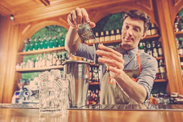 El experto barman está haciendo un cóctel en el club nocturno.