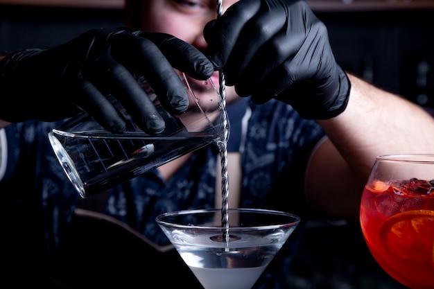Experto barman prepara un cóctel en un club nocturno