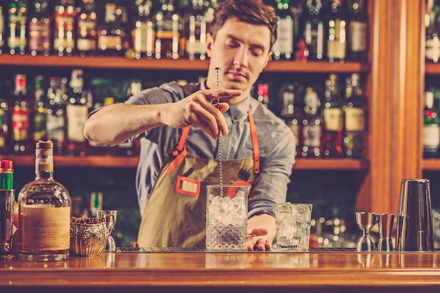 Un experto barman prepara cócteles en un club nocturno o bar.