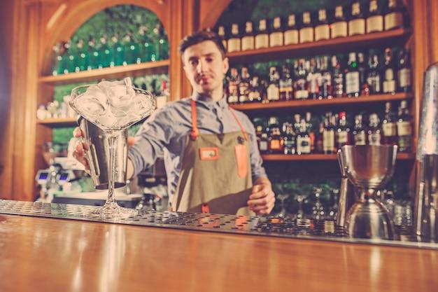 El experto barman prepara cócteles en un club nocturno.