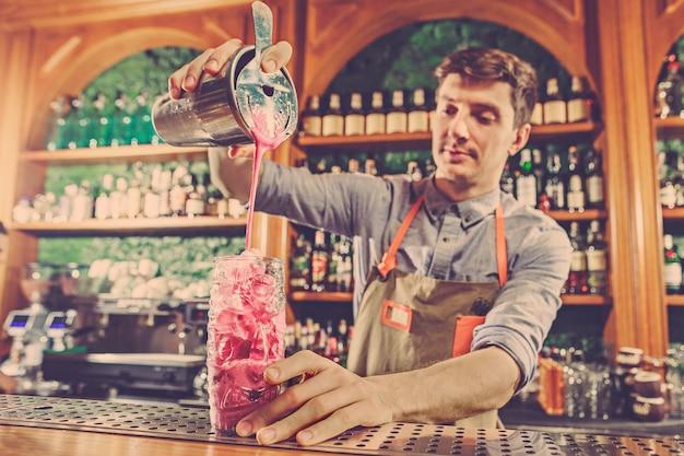 El experto barman prepara cócteles en el club nocturno.