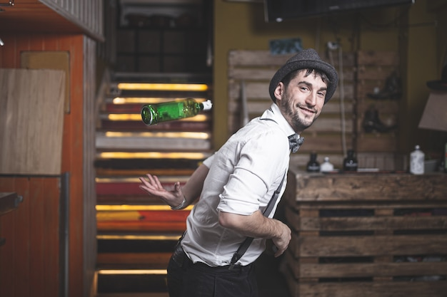 Experto barman con sombrero y pajarita lanzando una botella al aire