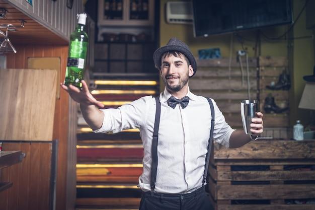 Experto barman con sombrero y pajarita sosteniendo una botella
