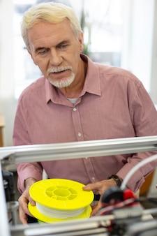 Experto en la materia. hombre senior agradable sosteniendo un carrete de filamento para impresora 3d y comprobando el rendimiento de una impresora 3d