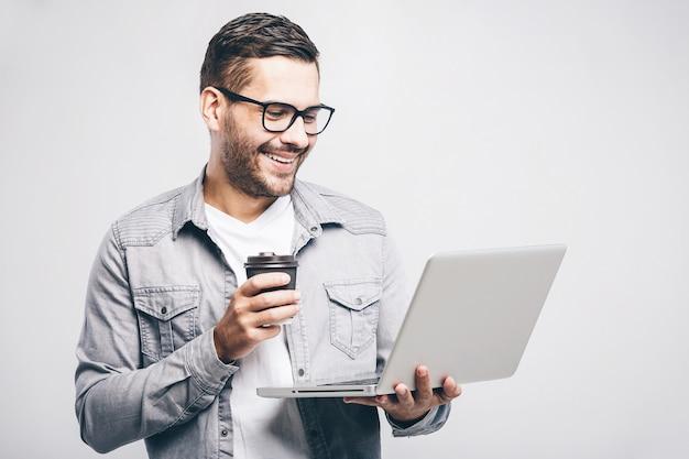 Experto en negocios confiados. hombre guapo joven confidente en camisa sosteniendo portátil y sonriendo mientras está de pie contra el fondo blanco