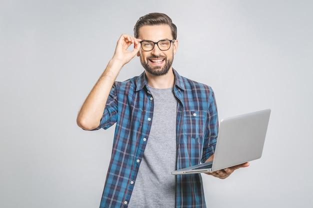 Experto en negocios seguros. hombre guapo joven confidente en camisa con laptop y sonriendo mientras está de pie contra la pared gris