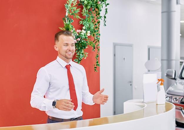 Experto en ventas caucásico sonriente dando la bienvenida a los clientes en el showroom de automóviles