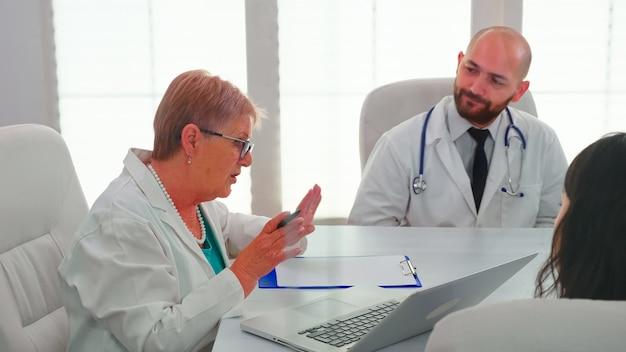 Expertos médicos que tienen seminario de salud en la sala de conferencias del hospital, discutiendo sobre los síntomas de los pacientes. el terapeuta de la clínica habla con sus colegas sobre la enfermedad para el desarrollo del tratamiento.