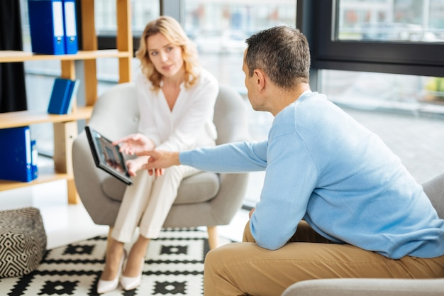 Explícame esto. hombre guapo agradable inteligente sentado frente a su terapeuta y apuntando a la tableta mientras le pide que le explique su diagnóstico