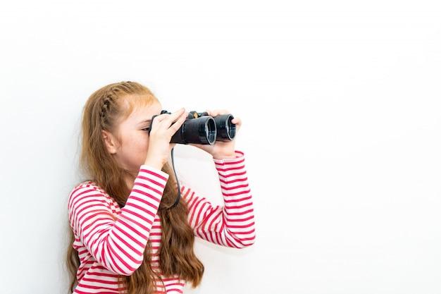 El explorador de la niña está mirando a través de los prismáticos
