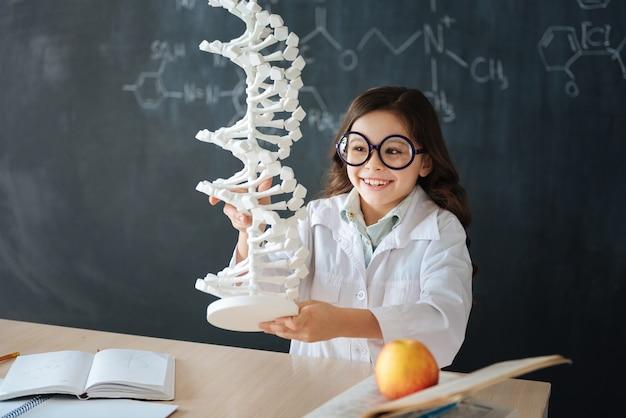 Explorando modificaciones del código genético. niña sonriente dotada sentada en el laboratorio y disfrutando de la clase de microbiología mientras estudia y sostiene el modelo de código genético