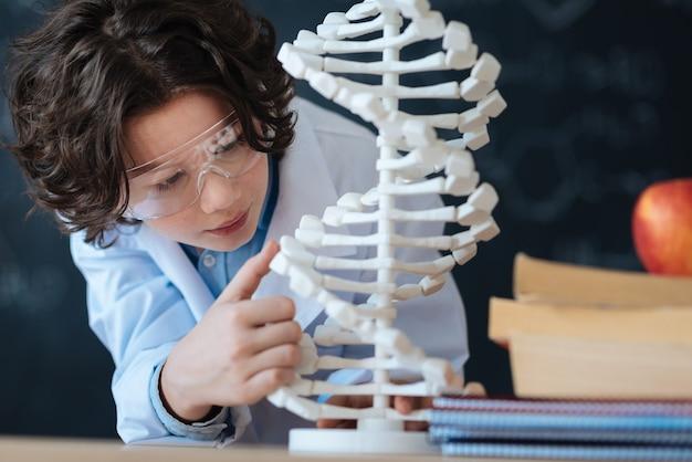 Explorando el mundo de la microbiología. pequeño investigador entusiasta inteligente de pie en el laboratorio y mirando el modelo de código genético mientras estudia bioingeniería y trabaja en el proyecto