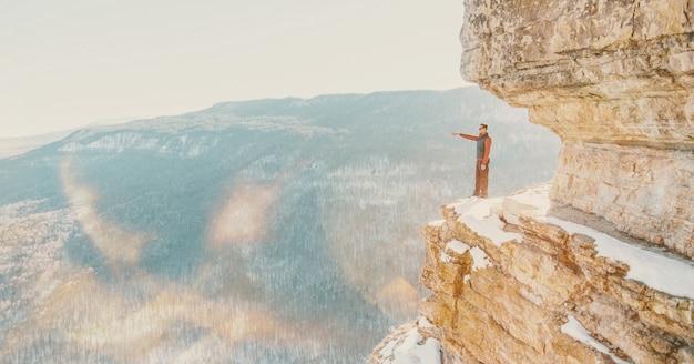 Explorer hombre parado en el acantilado eagle estante