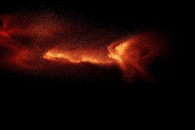 Explosión abstracta de polvo naranja sobre negro