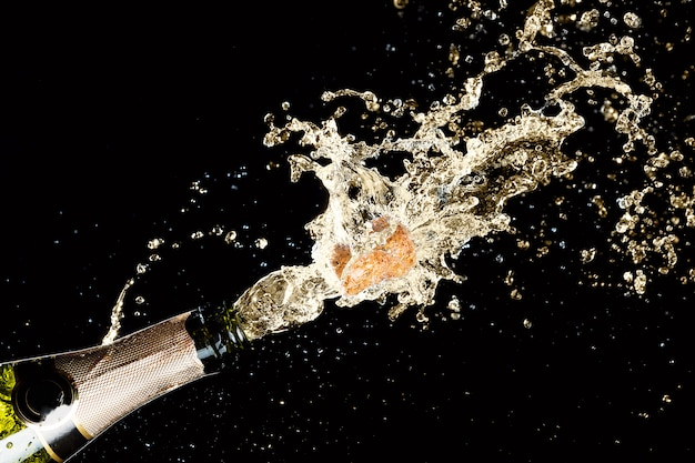 Explosión de champán salpicando vino espumoso