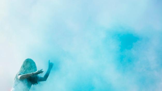 Explosión de color azul holi sobre la joven bailando.
