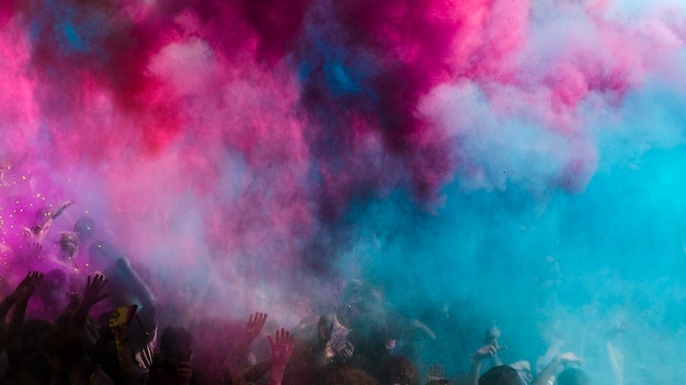 Explosión de color azul y rosa holi sobre la multitud