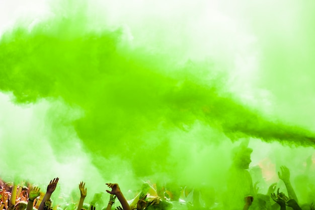 Explosión de color verde holi sobre la multitud.