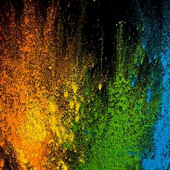 Explosión de colores holi sobre superficie negra.