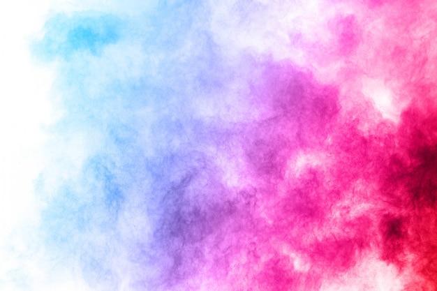 Explosión colorida del polvo en el fondo blanco.