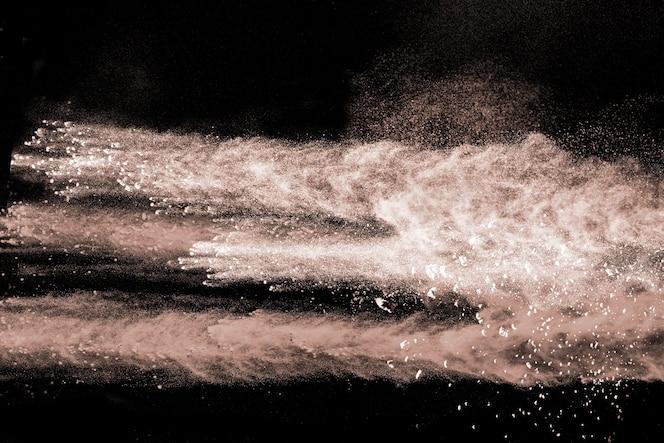 Explosión de polvo de color marrón sobre fondo negro.