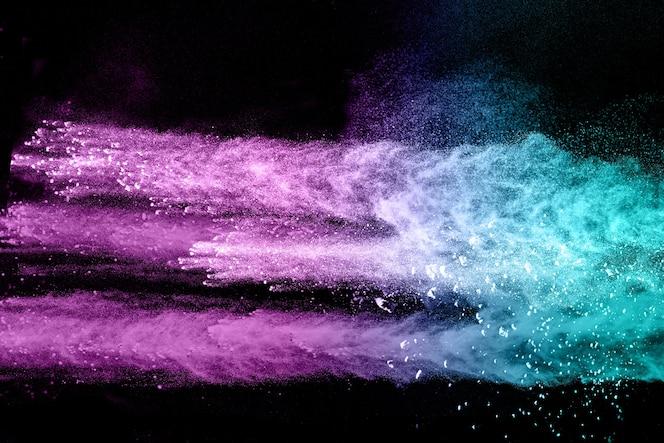 Explosión de polvo multicolor sobre fondo negro.