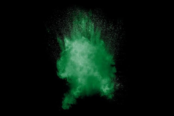 Explosión de polvo verde sobre fondo negro.