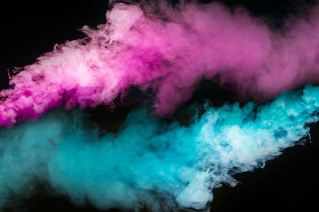 Explosión de humo azul y rosa sobre fondo negro.