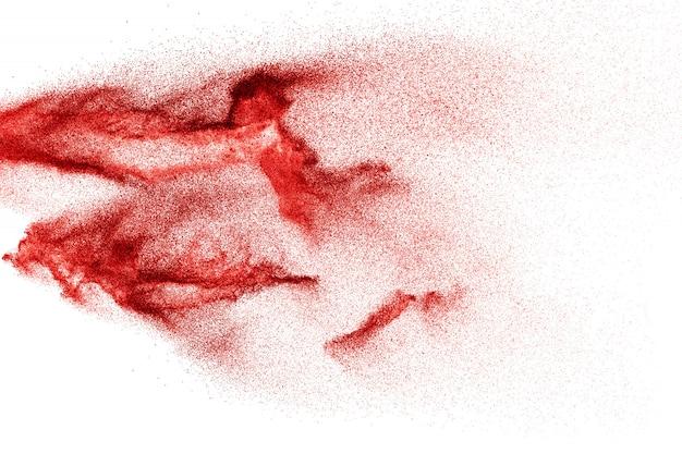 Explosión de partículas de polvo rojo sobre superficie blanca