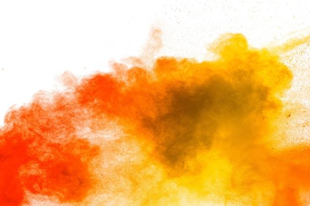 Explosión de polvo amarillo rojo sobre fondo blanco. nubes de salpicaduras de polvo de color amarillo rojo.