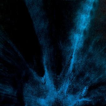 Explosión de polvo azul sobre fondo negro