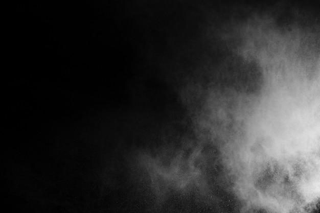 Explosión de polvo blanco sobre fondo negro.