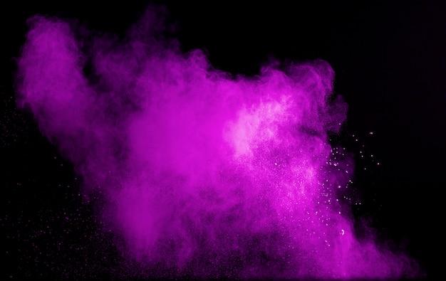 Explosión de polvo de color púrpura sobre fondo negro.