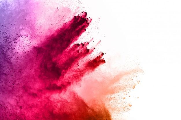 Explosión de polvo de colores sobre fondo blanco.