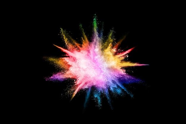 Explosión de polvo de colores sobre fondo negro.
